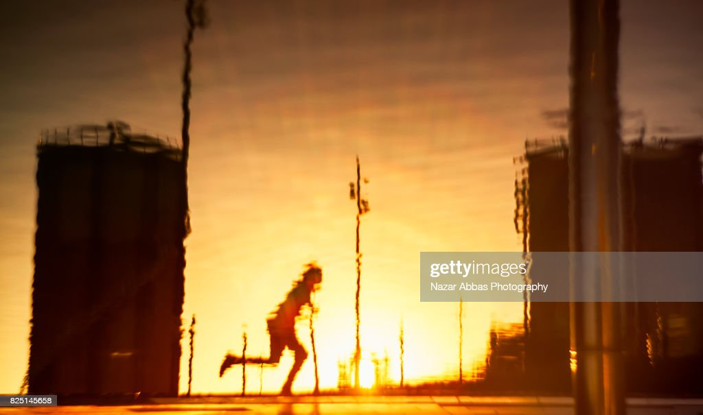 Reflection of a skateboarder with sunset in background. : Stock Photo