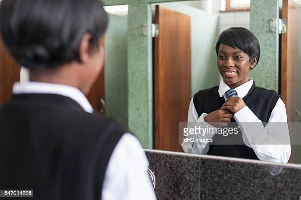 Reflection of a student fixing her tie in the bathroom mirror, Cape Town, South Africa