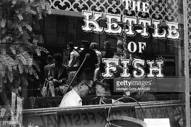 A reflection of a wagon promoting the New York Folk Festival can be seen in the window of The Kettle of Fish restaurant a favorite hangout of Bob...