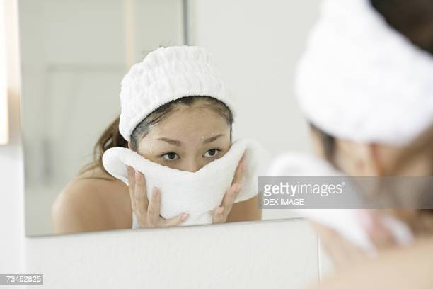 Reflection of a young woman drying her face with a towel in a mirror