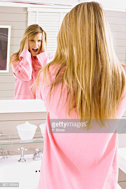 reflection of a young woman looking in mirror and shouting - focus on background stock pictures, royalty-free photos & images