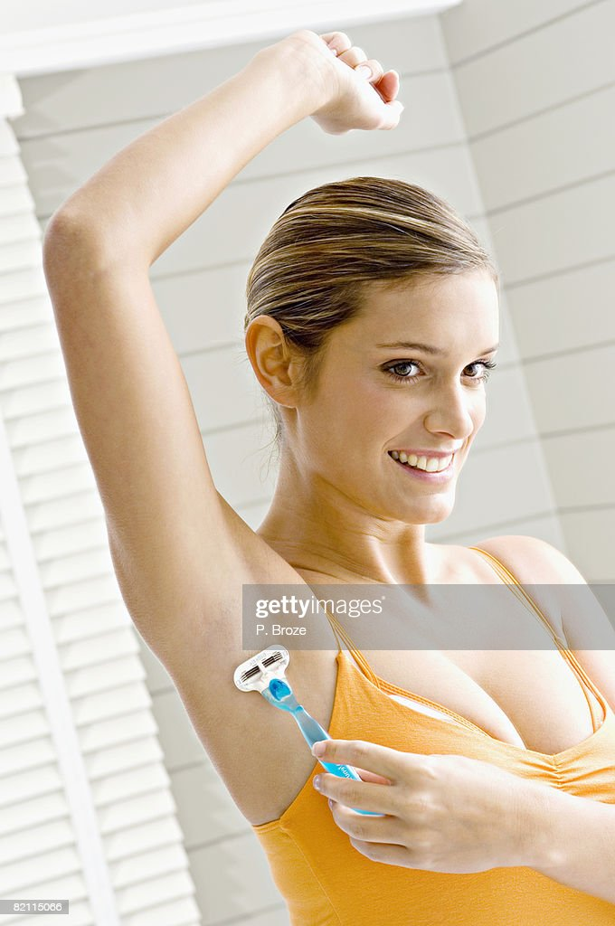 Reflection of a young woman shaving her armpit hair : Stock Photo