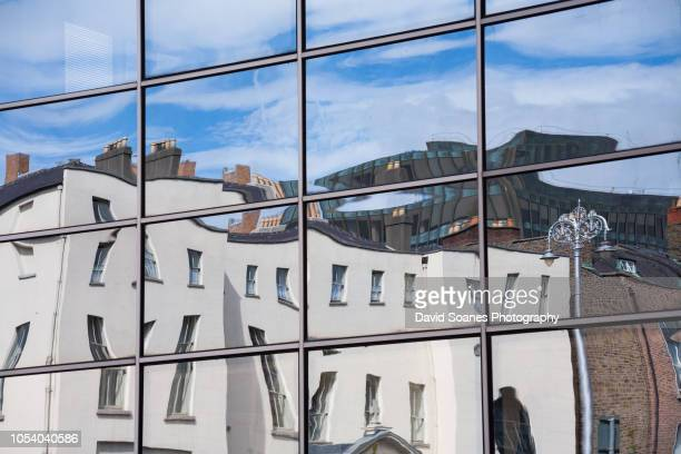 a reflection of an office building in a window in dublin, ireland - distorted image stock pictures, royalty-free photos & images