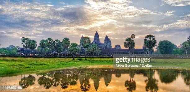 reflection of angkor wat temple on lake against cloudy sky - アンコールワット ストックフォトと画像