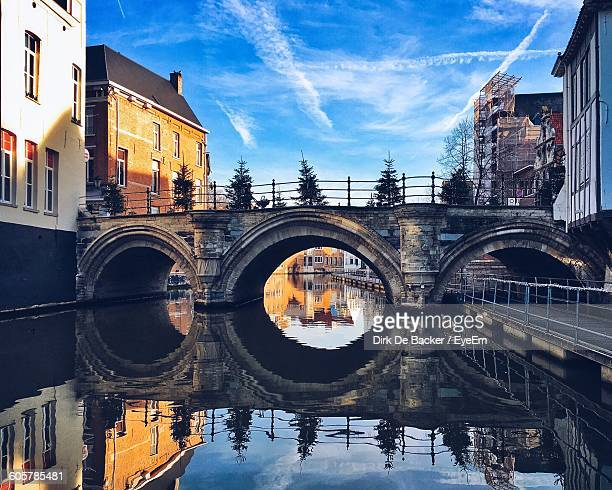 reflection of arch bridge on river amidst buildings in city - mechelen stock pictures, royalty-free photos & images