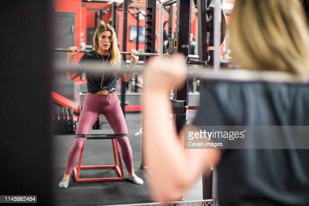 reflection of attractive woman training on squat rack at gym. - athletic club fotografías e imágenes de stock