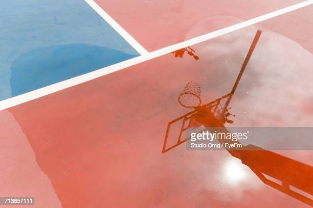 Reflection Of Basketball Hoop At Court In Puddle
