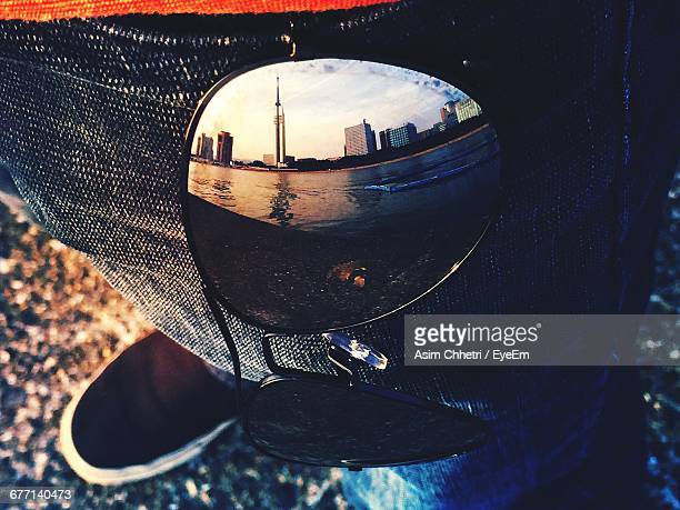 reflection of beach and buildings on sunglasses in jeans pocket worn by man - fukuoka city stock pictures, royalty-free photos & images