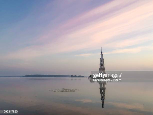 reflection of bell tower in river at kalyazin - volga stock pictures, royalty-free photos & images
