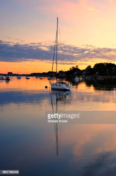 reflection of boat in bay, newport, ri - newport rhode island stock pictures, royalty-free photos & images