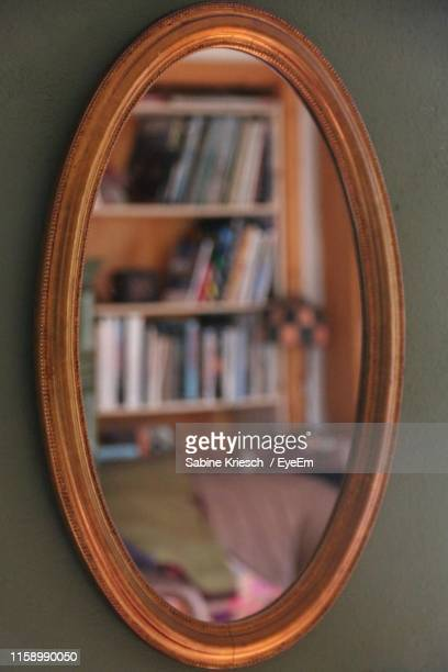 reflection of bookshelf in mirror at home - sabine kriesch stock-fotos und bilder