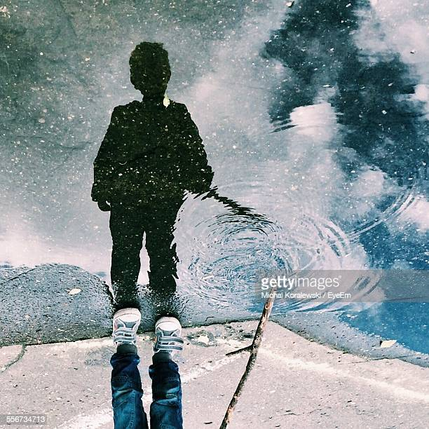 reflection of boy in puddle - puddle stock pictures, royalty-free photos & images