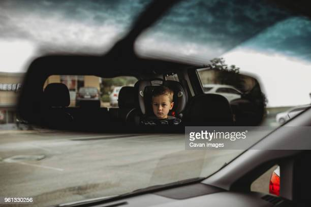 reflection of boy on rear-view mirror in car - rear view mirror stock pictures, royalty-free photos & images
