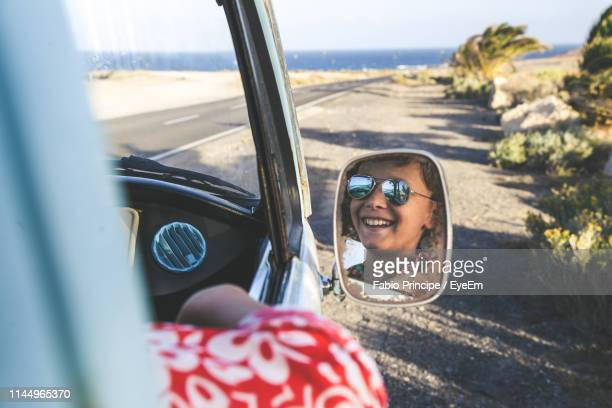 reflection of boy on side-view mirror - side view mirror stock photos and pictures