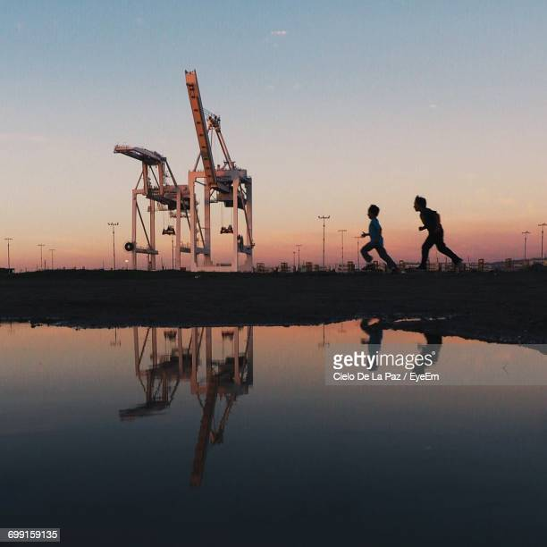 reflection of boys running by calm lake against crane during sunset - cielo stock pictures, royalty-free photos & images