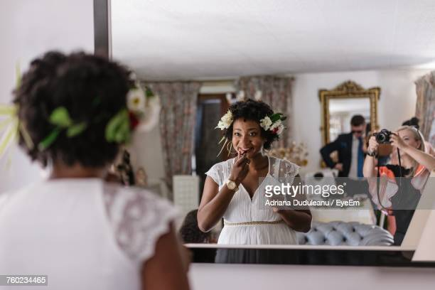 reflection of bride applying lipstick while standing in front of mirror - figurantes incidentais - fotografias e filmes do acervo