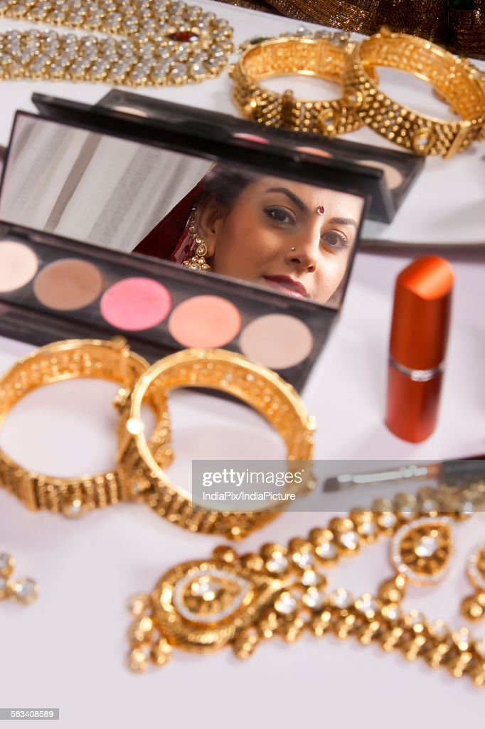 Reflection of brides face in makeup mirror : Stock Photo