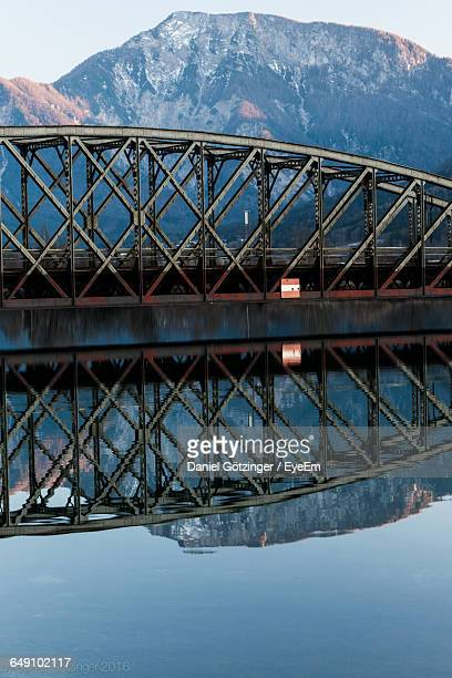 Reflection Of Bridge And Mountains In River At Dusk