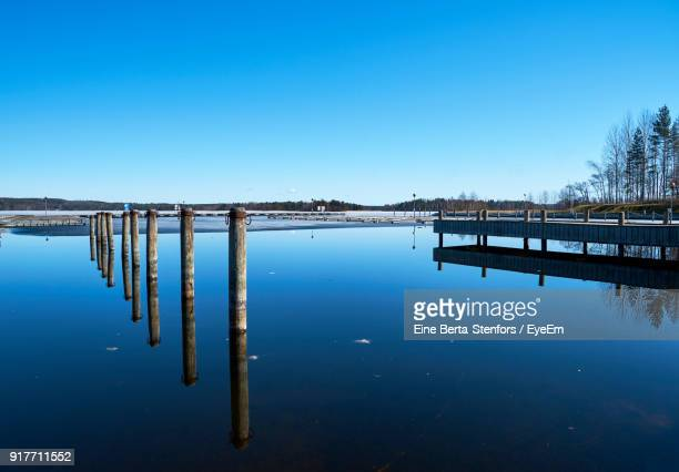 Reflection Of Bridge On River Against Clear Blue Sky