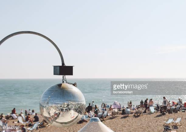 reflection of brighton beach on disco ball against clear sky - bortes stockfoto's en -beelden