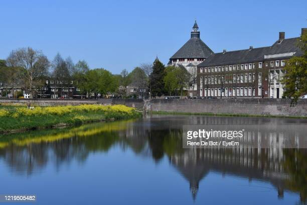 reflection of building and trees in lake against clear blue sky - 's hertogenbosch stockfoto's en -beelden