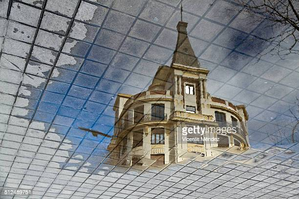 reflection of building in a puddle on the sidewalk - vicente méndez fotografías e imágenes de stock