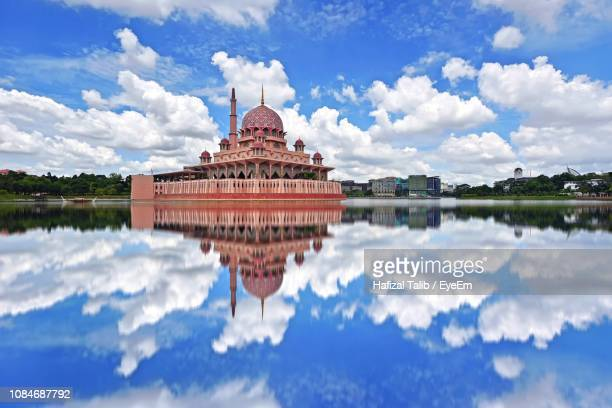 reflection of building in lake against cloudy sky - putrajaya stock photos and pictures