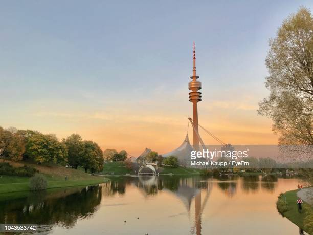reflection of building in lake at sunset - münchen stock-fotos und bilder