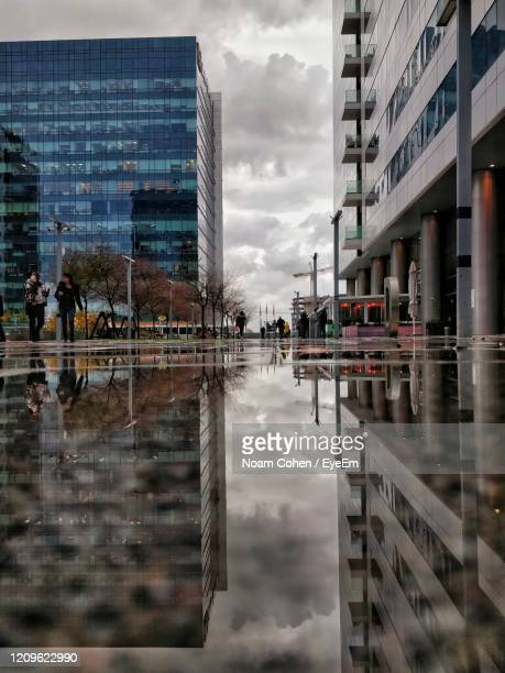 reflection of building in puddle on glass - noam cohen stock pictures, royalty-free photos & images