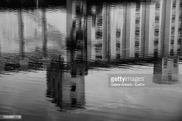 reflection of building in puddle on lake - sabine kriesch stock-fotos und bilder