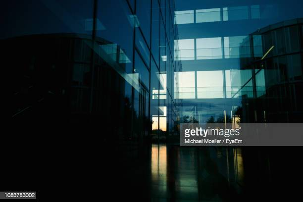 reflection of building on glass window - spiegelung stock-fotos und bilder