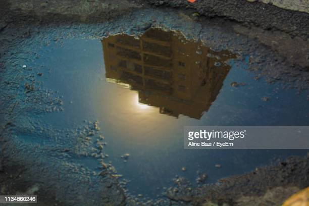 reflection of building on puddle in lake - rua stock pictures, royalty-free photos & images