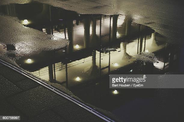Reflection Of Building On Puddle In Street