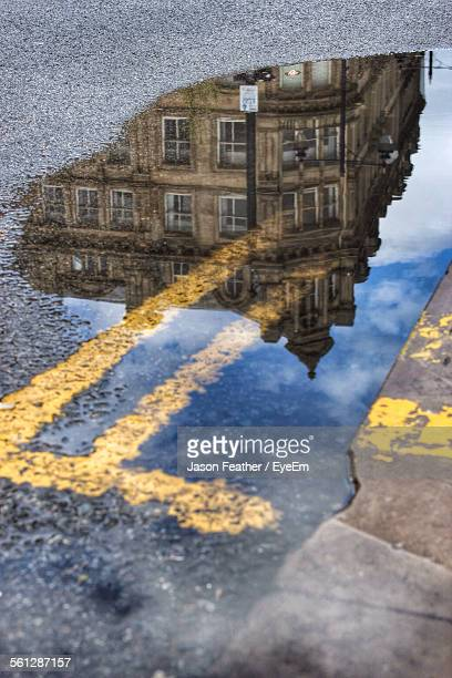 reflection of building on puddle - bradford england stock pictures, royalty-free photos & images