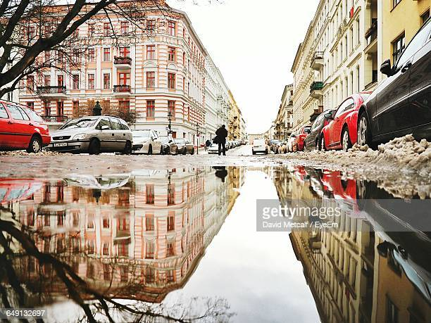 Reflection Of Buildings And Cars In Puddle On Street