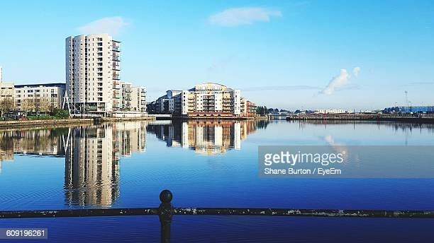 Reflection Of Buildings In Calm Water Against Sky