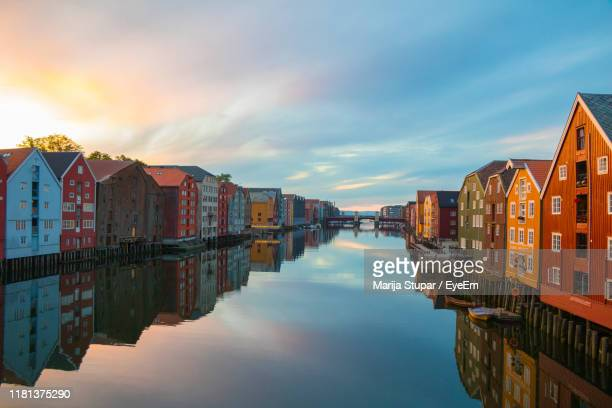 reflection of buildings in canal against sky - トロンハイム ストックフォトと画像