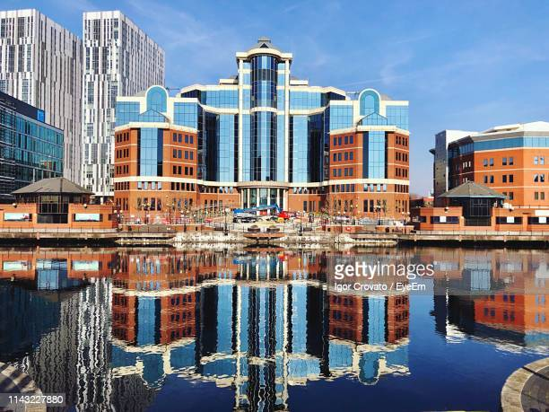 reflection of buildings in city against sky - waterfront stock pictures, royalty-free photos & images