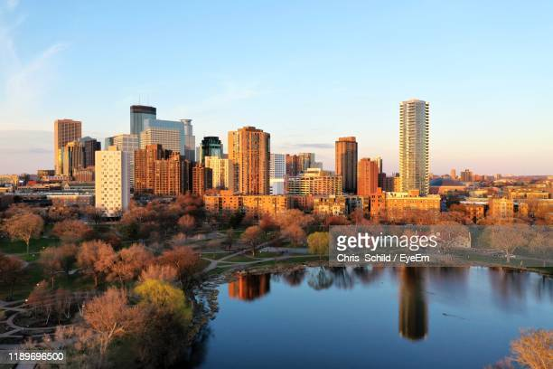 reflection of buildings in city against sky - minneapolis stock pictures, royalty-free photos & images