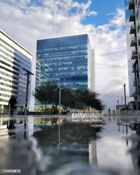 reflection of buildings in city against sky - noam cohen stock pictures, royalty-free photos & images