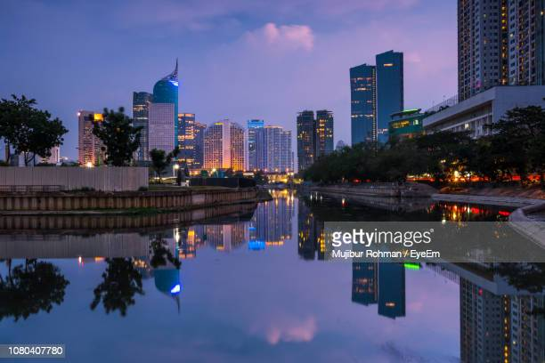 reflection of buildings in city at dusk - jakarta stock pictures, royalty-free photos & images