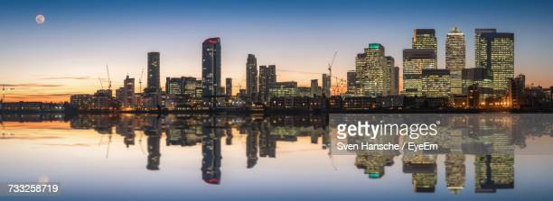 reflection of buildings in city at waterfront - canary wharf stock photos and pictures