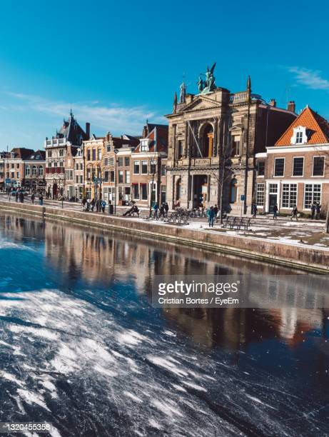 reflection of buildings in frozen water - bortes stock pictures, royalty-free photos & images