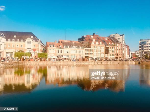 reflection of buildings in lake against blue sky - france lille stock pictures, royalty-free photos & images