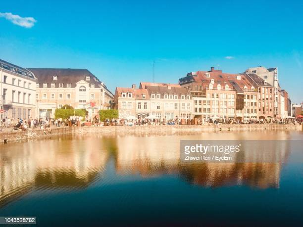 reflection of buildings in lake against blue sky - lille stock pictures, royalty-free photos & images