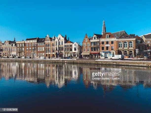 reflection of buildings in lake against clear blue sky - bortes stock pictures, royalty-free photos & images