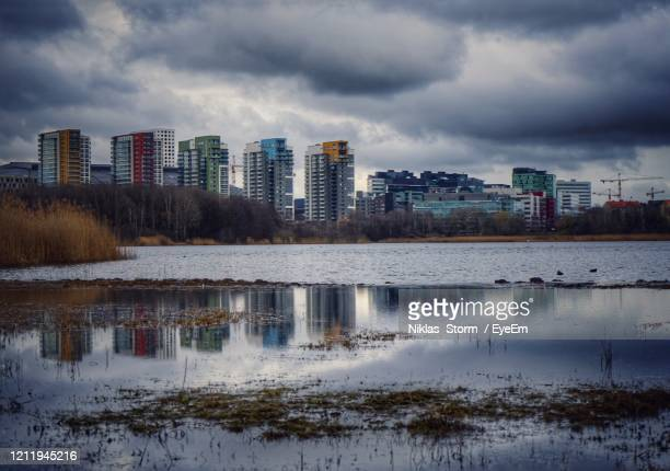 reflection of buildings in lake against cloudy sky - ソルナ ストックフォトと画像