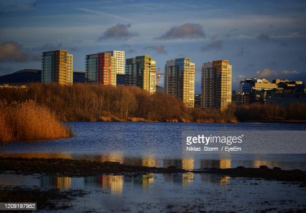 reflection of buildings in lake against sky at sunset - ソルナ ストックフォトと画像