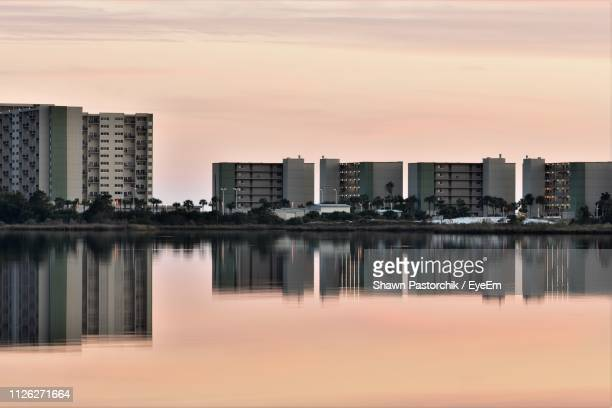 reflection of buildings in lake against sky during sunset - panama city beach stock pictures, royalty-free photos & images