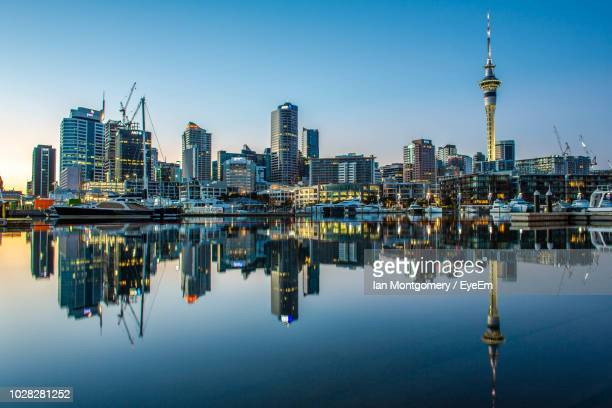 reflection of buildings in lake against sky - auckland stock pictures, royalty-free photos & images